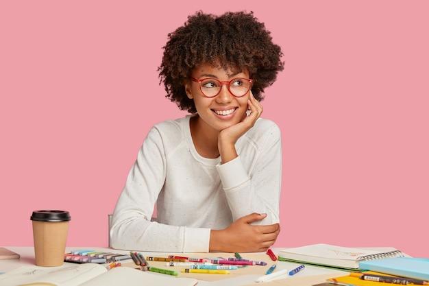 Soddisfatto carino allegro felice designer femminile sogna qualcosa di piacevole durante la pausa caffè, tiene la mano sulla guancia, indossa un maglione bianco, crea un nuovo progetto, isolato su un muro rosa.