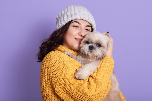 Satisfied dark haired female with her puppy looks at camera with cute facial expression