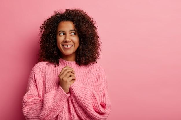 La ragazza dalla pelle scura soddisfatta con i capelli ricci afro tiene le mani unite, concentrata sopra i sorrisi indossa delicatamente i sogni di maglione lavorato a maglia su qualcosa di carino ha un'espressione premurosa allegra isolata sul rosa