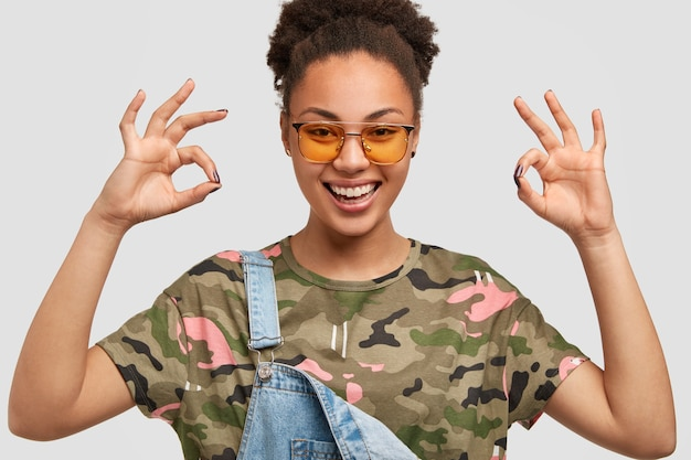 Satisfied dark skinned young woman keeps hands in okay gesture, dressed in casual camouflage t-shirt, denim overalls