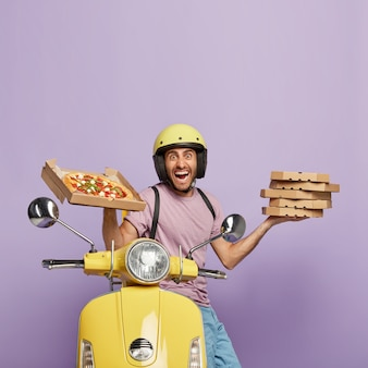 Satisfied deliveryman driving yellow scooter while holding pizza boxes