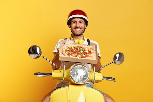 Satisfied deliveryman with helmet driving yellow scooter while holding pizza box