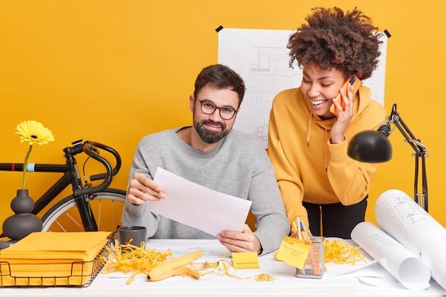 만족 한 다양한 여성과 남성은 사무실에서 즐거운 시간을 보내고 창의적인 프로젝트를 준비하면서 현대적인 공간에서 공동 작업을 진행하고 서류 작업을 통해 스케치와 청사진을 만듭니다. 바탕 화면 근처 두 건축가
