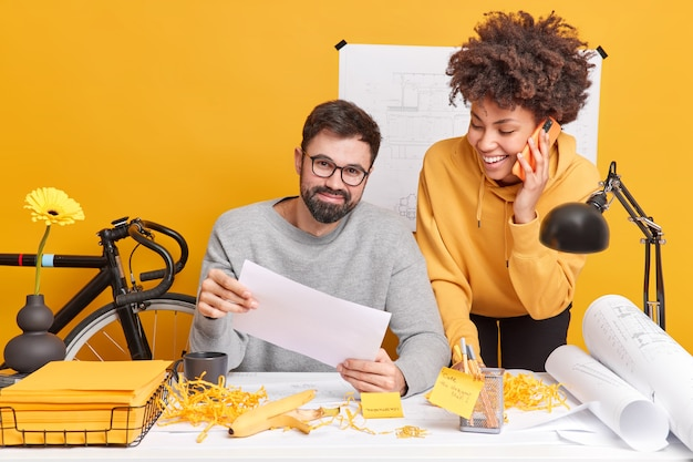 Satisfied diverse woman and man have fun in office while preparing creative project collaborate for common task at modern space do paperwork create sketches and blueprints. two architects near desktop