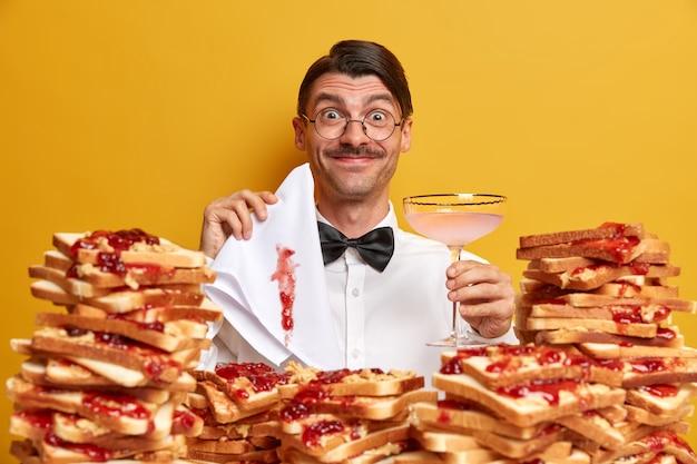 Soddisfatto elegante uomo nerd beve cocktail, vestito con camicia bianca con farfallino, essendo al banchetto, tiene il tovagliolo bianco come la neve sporco di marmellata, pone vicino al mucchio di pane, isolato sul muro giallo