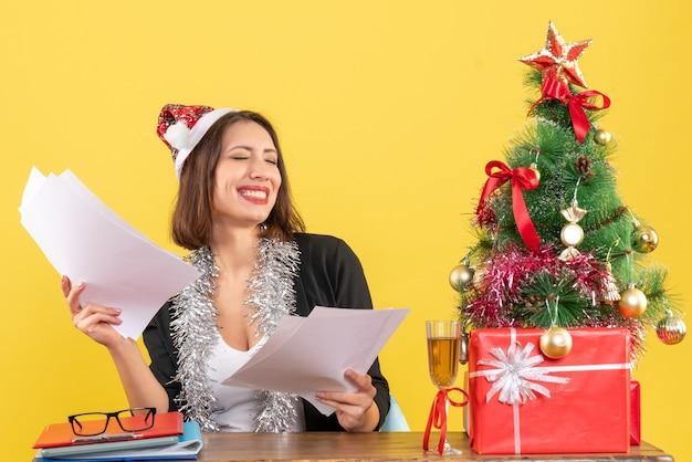 Soddisfatta donna d'affari emotiva in vestito con cappello di babbo natale e decorazioni di capodanno che tiene documenti e seduta a un tavolo con un albero di natale su di esso in ufficio