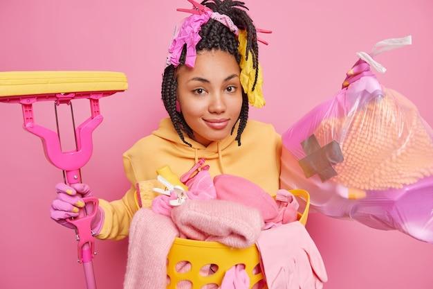 三つ編みにゴム手袋をはめて満足している民族の女性はごみ袋を保持します