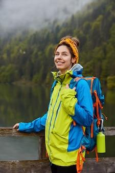 満足しているヨーロッパの女性旅行者は、レクリエーションの時間を楽しんだり、美しい川の近くを歩いたりします