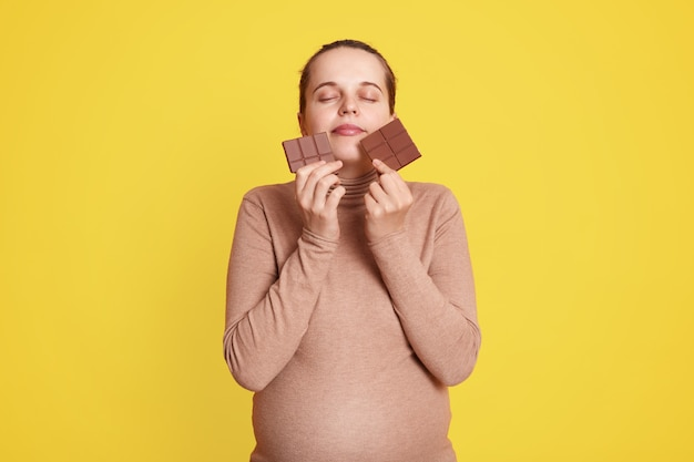 Satisfied expectant mother standing against yellow wall with closed eyes, holding bars of chocolate in both hands