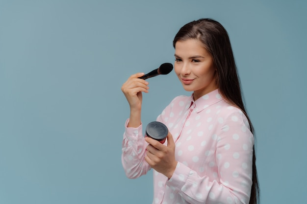 満足している女性美容師はブラシで化粧をし、高品質の化粧品を使用しています