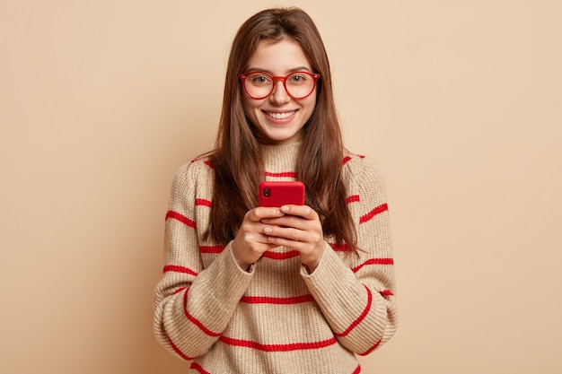 Satisfied female blogger enjoys chatting online, has pleasant smile, downloads new application on smartphone device, wears spectacles and casual jumper, poses over beige wall, receives email