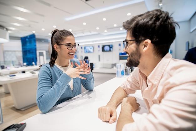계산원이 기술 매장에서 일하는 남자와 이야기하는 만족스러운 여성 고객.