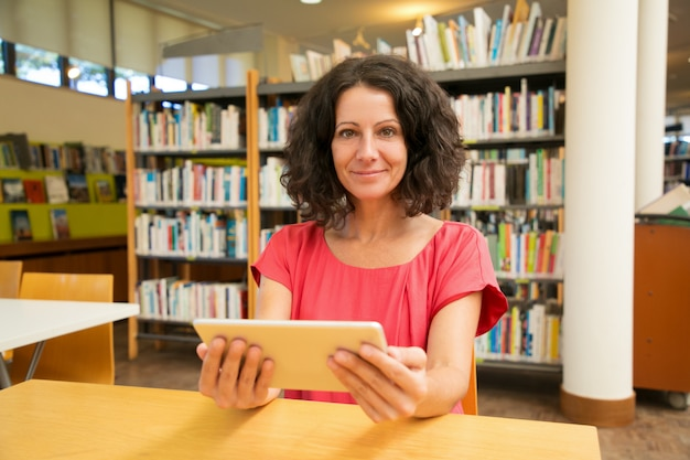 Cliente femminile soddisfatto con l'aggeggio che posa nella biblioteca pubblica
