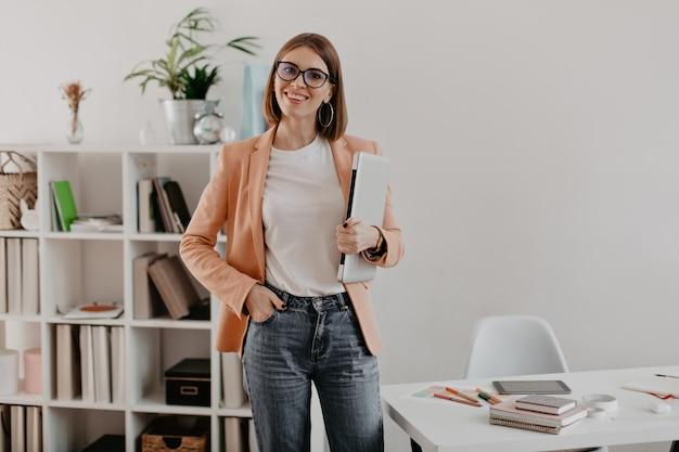 그녀의 최소한의 사무실에 대해 노트북을 손에 들고 포즈를 취하는 만족 된 여성 기업가.