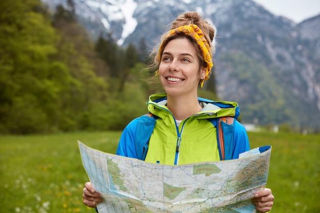 満足している女性探検家は、雪に覆われた山頂の山でヒッチハイク旅行をし、緑の丘を歩いて歩き、カラフルなアノラックを着ています