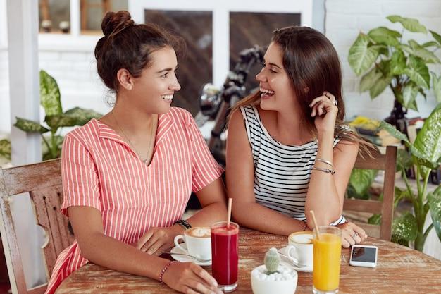 만족 한 여자 친구들은 함께 즐거운 대화를 나누고 카페에 앉아 칵테일, 카푸치노, 스마트 폰으로 둘러싸여 레스토랑에서 여가 시간을 보냅니다. 즐거운 여성들이 재미로 뭔가 토론
