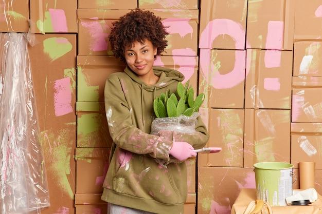 満足している女性の住宅所有者は、カジュアルなスウェットシャツに身を包んだ新しい家で修理をするのに忙しいペイントブラシと鉢植えのサボテンを持って、嬉しい表情で壁のスタンドを改装します。インテリアのリノベーション