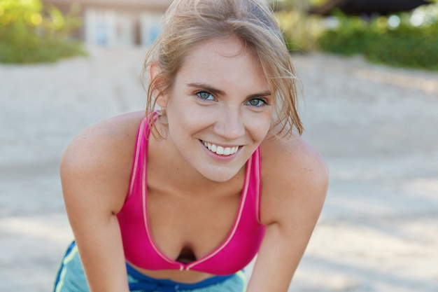 Satisfied female jogger catches breathe after active morning running, glad to have sport motivation, spends free time on fresh air dressed in sport bra. workout outdoors. people and lifestyle concept