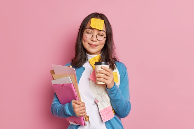 Satisfied female manager works with paper documents has coffee break closes eyes sticky note with drawn graphic stuck to forehead wears round spectacles.