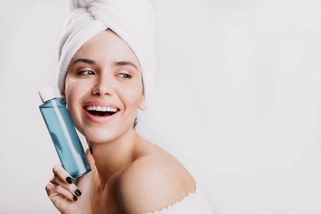 Satisfied female model without makeup smiling on white wall. girl after shower posing with bottle of cosmetic tonic.
