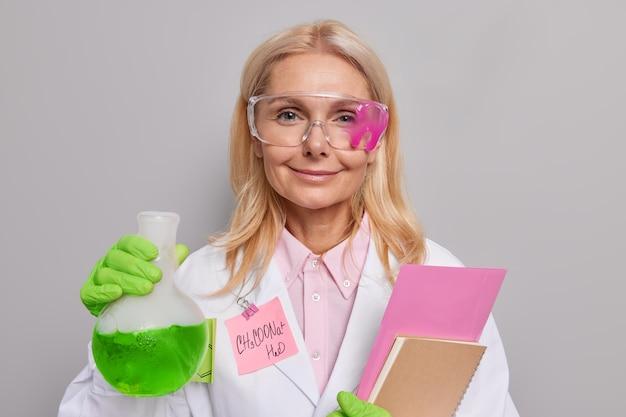 만족한 여성 연구원은 흰색 의료용 안경을 쓰고 메모를 작성하기 위해 녹색 액체 노트북이 있는 유리 플라스크를 들고 회색으로 격리된 과학 실험을 수행합니다