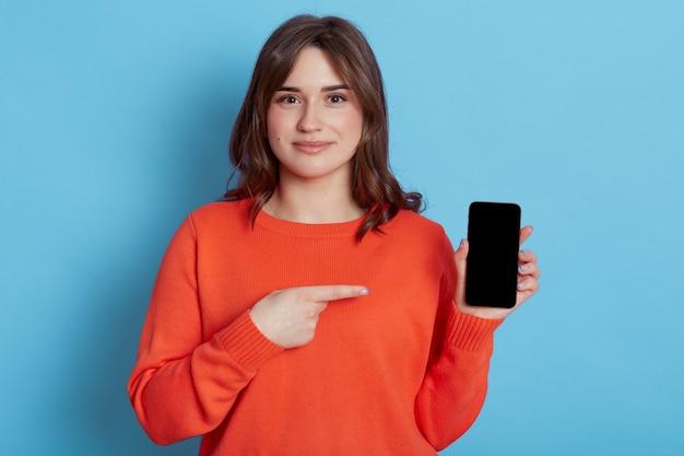 손에 스마트 폰으로 서 있고 파란색 벽 위에 절연 검지 손가락으로 빈 화면에서 가리키는 만족 된 여성.