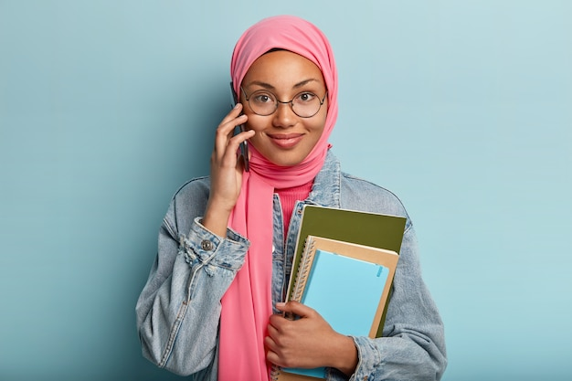Satisfied female talks on mobile phone, spends free time gossiping, feels pleased, holds notepads, wears fashionable denim clothes, has covered head with pink veil, isolated over blue wall