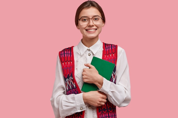 Satisfied female teacher in elegant neat clothes, wears big optical glasses, holds green notebook, glad to meet pupils after summer holidays, isolated on pink wall. cheerful nerd on lecture.