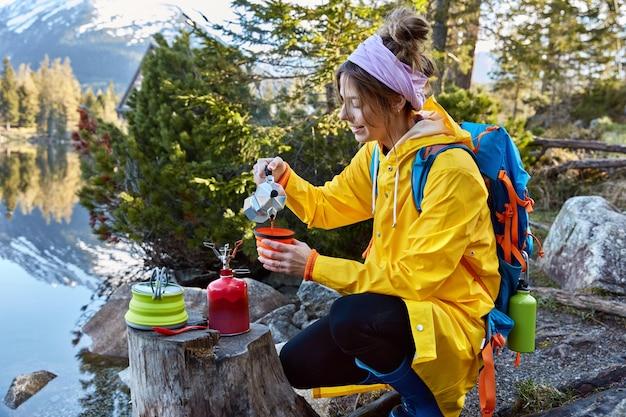Una viaggiatrice soddisfatta versa il caffè dalla macchina per il caffè nella tazza da tè, utilizza una bottiglia di butano da campeggio rossa, indossa un impermeabile con zaino