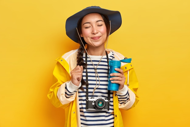 Viaggiatore soddisfatto con aspetto asiatico, indossa cappello, maglione a righe e impermeabile, retro macchina fotografica sul collo, tiene la bottiglia di bevanda calda, isolato sopra il muro giallo
