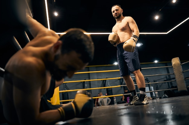 Satisfied fighter standing in the middle of the ring looking at his partner, lying on the floor in the corner