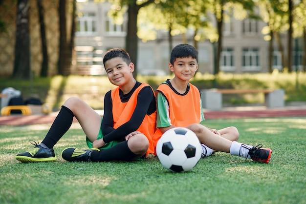 Довольный футболист отдыхает на спортивном поле после тренировки.
