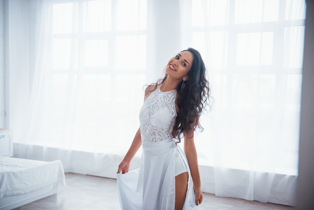 Satisfied and free. beautiful woman in white dress stands in white room with daylight through the windows