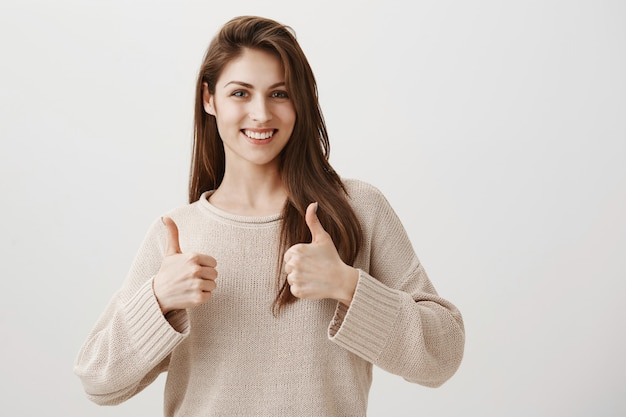 Satisfied girl showing well done thumbs-up gesture, smiling pleased