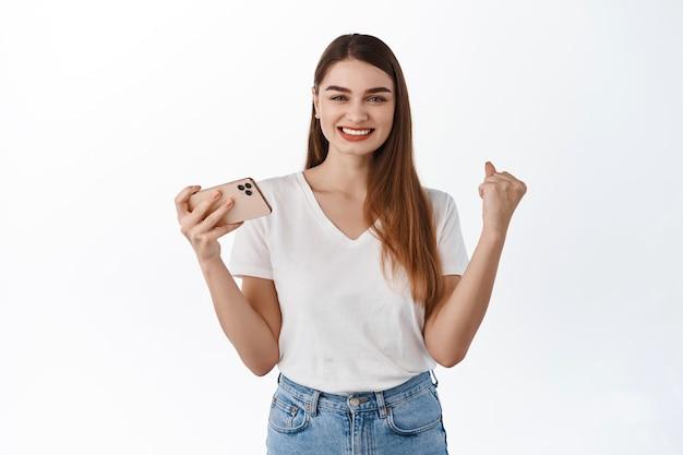 満足している女の子がスマートフォンで勝ち、携帯電話を手に喜んで、「はい」と言って、喜んで幸せそうに見え、アプリケーションで目標を達成し、成功を祝い、白い壁の上に立って
