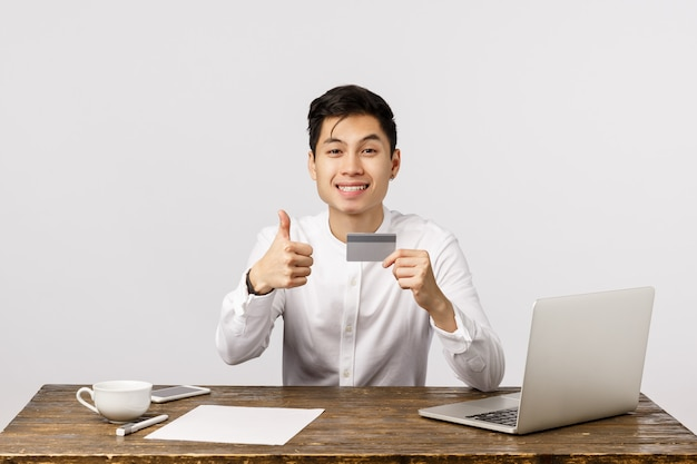 Satisfied good-looking asian office worker, manager sitting desk with documents, laptop and cup coffee, holding credit card, show thumbs-up and smiling, recommend buy online and use bank service