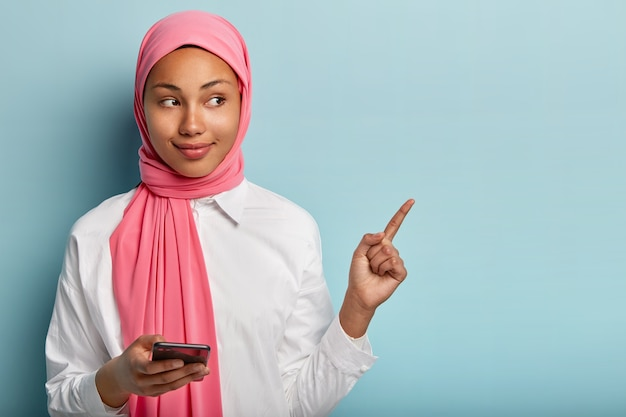 Satisfied good looking female with dark skin, holds cell phone, chats with followers in social networks, points away fore finger, demonstrates free space for promotional content, wears scarf on head