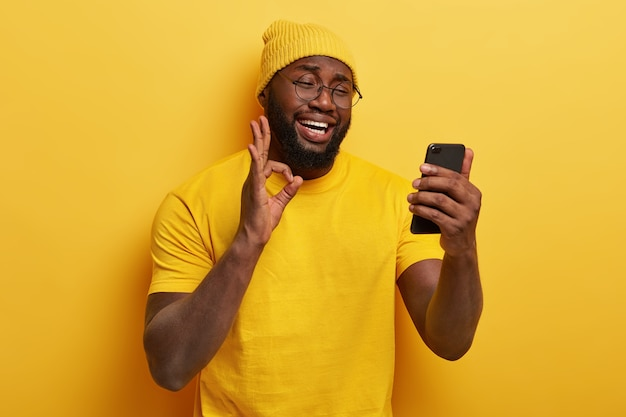 Довольный красивый парень в очках позирует со своим телефоном