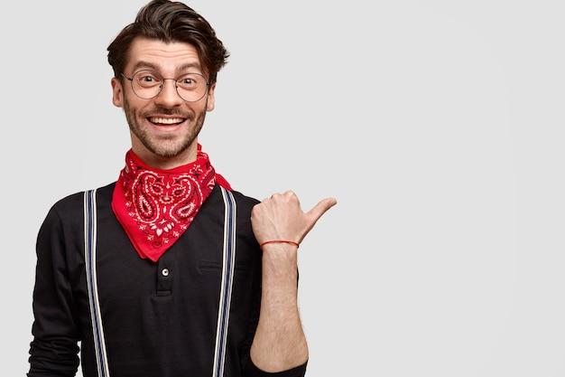 ファッショナブルな服を着て満足しているハンサムな男は、あなたに方向を示して幸せで、親指で脇を向いて、楽しい表情と魅力的な笑顔を持っています