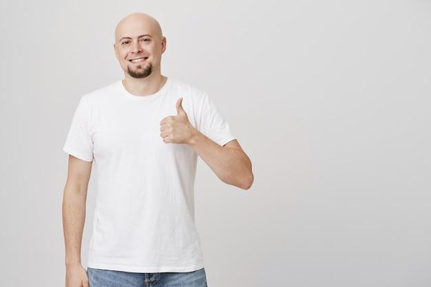 ハゲの頭を持つ満足しているハンサムな中年男は親指を立て、喜んで笑顔