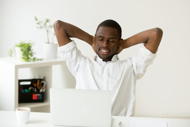 Satisfied happy african american man relaxing with coffee and laptop