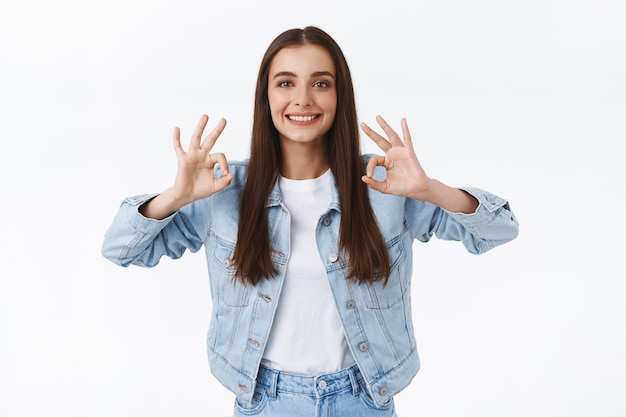 Satisfied happy attractive brunette girl in denim jacket, showing ok, okay sign, smiling and nod in approval, pleased with good outcome, give positive reply, think plan excellent, white background