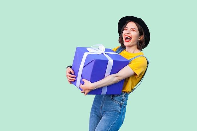 Удовлетворенная счастливая красивая молодая девушка в хипстерской одежде в джинсовом комбинезоне и черной шляпе, стоящая и держащая большую тяжелую подарочную коробку с зубастой улыбкой и смеющимся, открытым ртом. студийный снимок, зеленый фон