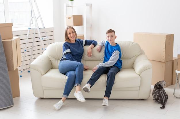 만족 한 행복 한 백인 미혼모와 아들이 새 아파트의 디자인을 논의하면서 행복하게 소통합니다.