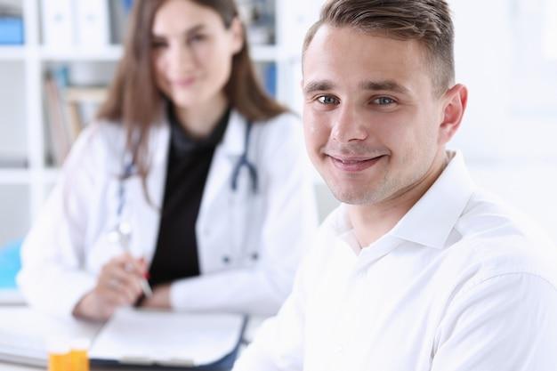 医者と満足した幸せなハンサムな笑顔の男性患者