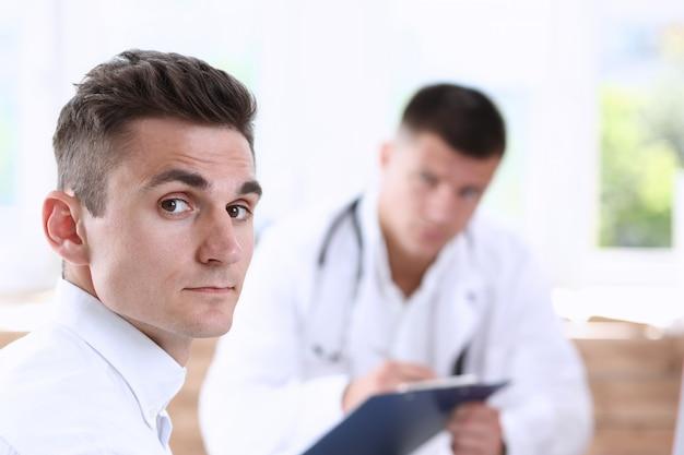 医師と満足している幸せなハンサムな笑顔の男性患者
