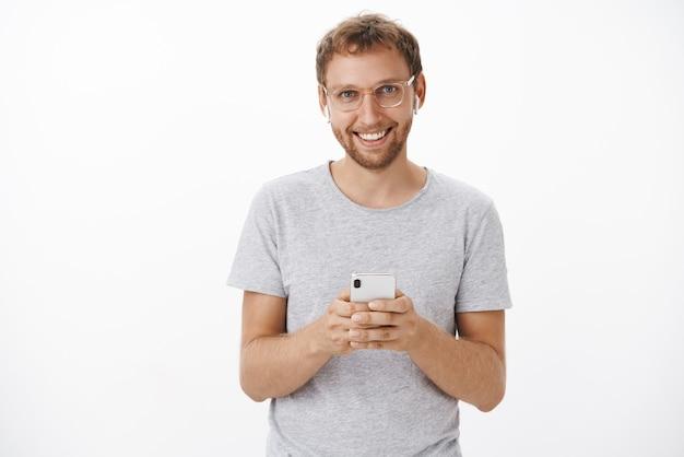 メガネの剛毛と灰色のtシャツを保持している満足している幸せな男性客は、高品質の音で喜んでいるワイヤレスイヤホンを着ている真新しいスマートフォンを保持しています。