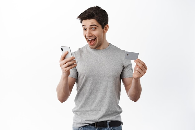 Satisfied happy man looking at smartphone screen, showing credit card, smiling excited, making online order, shopping in app, white wall