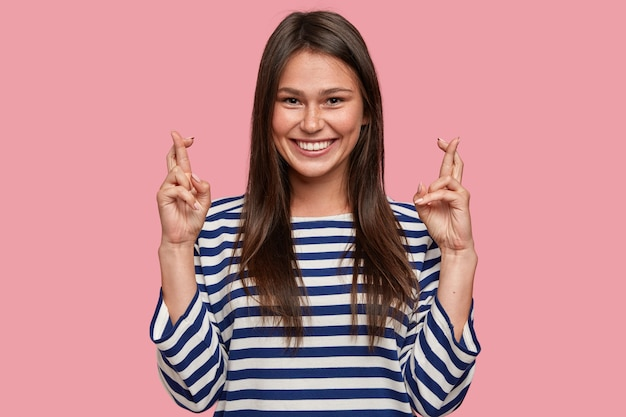 만족 한 행복 예쁜 여학생이 행운을 빌어 손가락을 교차하고 긍정적 인 표현을 가지고