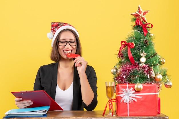満足のいく幸せな笑顔の魅力的な女性のスーツにサンタクロースの帽子と黄色の孤立したオフィスで銀行カードを示す眼鏡